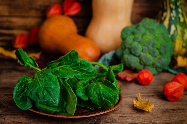 Verse spinazie op houten rustieke ruimte. kopieer ruimte. landelijk groentenstilleven