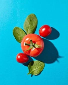 Verse spinaziebladeren en sappige rijpe tomaten op een blauw met harde schaduwen en exemplaarruimte. biologische groenten voor salade. plat leggen
