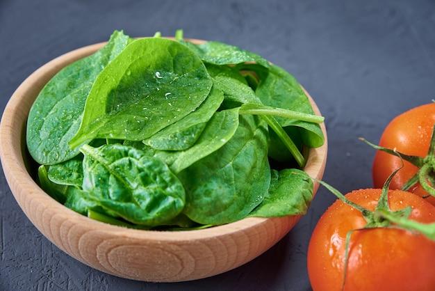 Verse spinaziebladeren in houten kom en tomaat op een donkere achtergrond. biologisch voedsel
