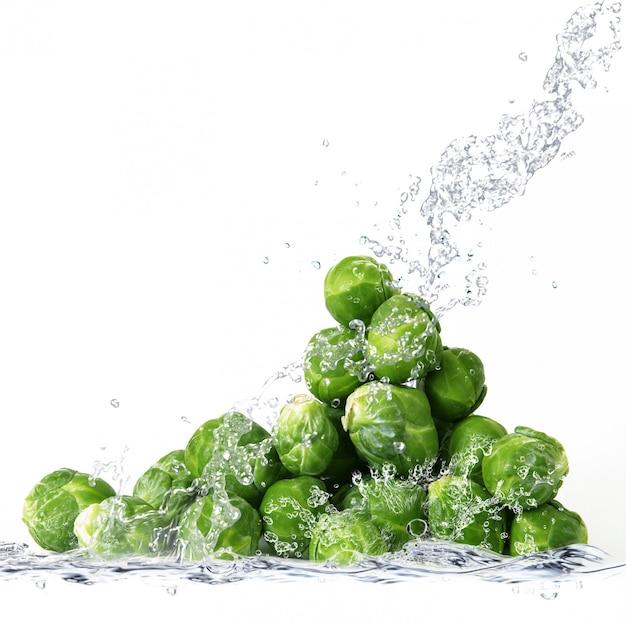 Verse spruitjes die in water vallen