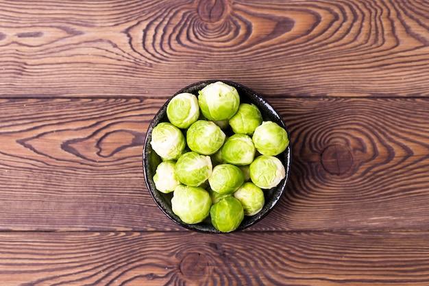 Verse spruitjes in een kom op een zwarte lei op een houten tafel. plaats voor tekst.