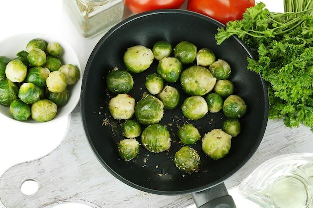 Verse spruitjes in pan met groenten en kruiden op wit