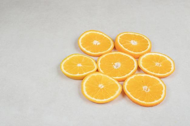 Verse stukjes sinaasappel op grijze ondergrond.