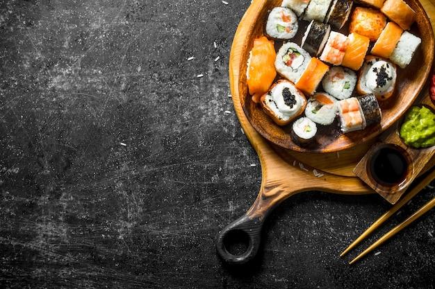 Verse sushi rolt in een plaat op een snijplank met stokjes en sauzen.