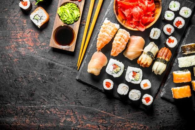 Verse sushibroodjes op zwarte steentribune. op donkere rustieke ondergrond
