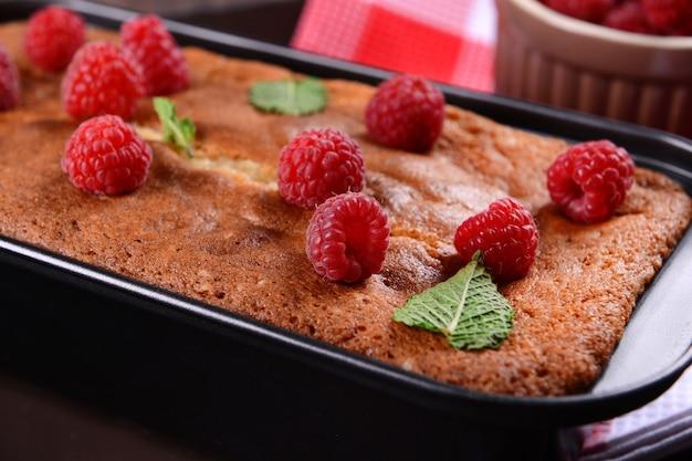Verse taart met framboos in pan op houten tafel, close-up