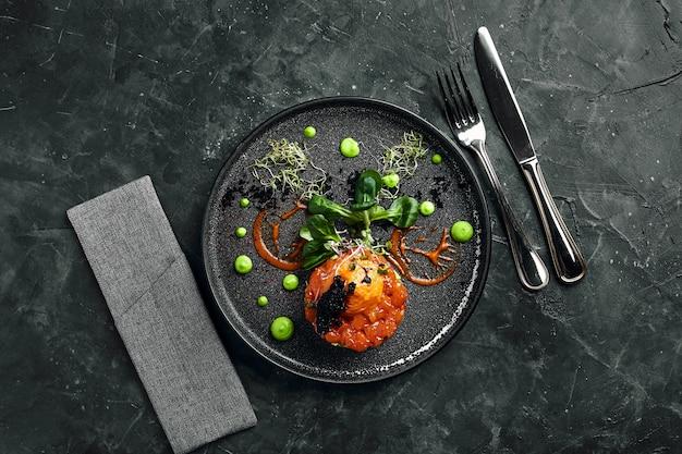 Verse tartaar met zalm, avocado, rode kaviaar op een bord, mooie portie, mooie portie, traditionele italiaanse keuken, kopie ruimte