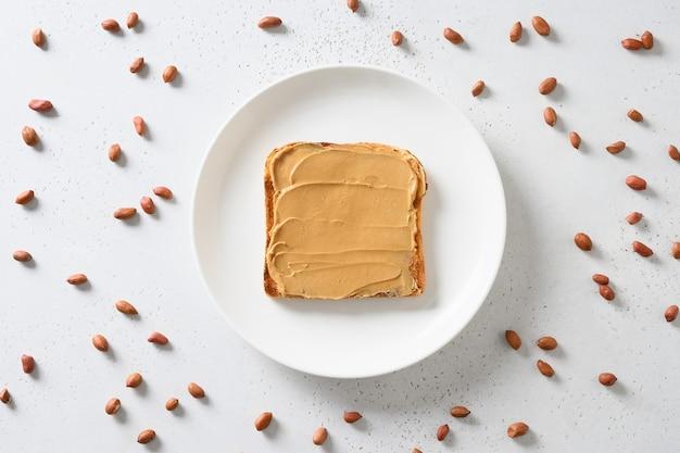 Verse toast met pindadeeg en noten rond op wit.