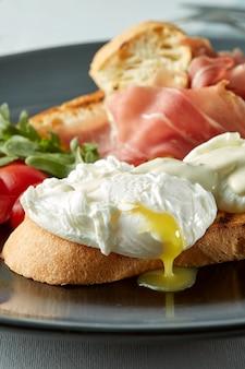 Verse toastsandwiches met gepocheerd ei, spek en salade in de plaat