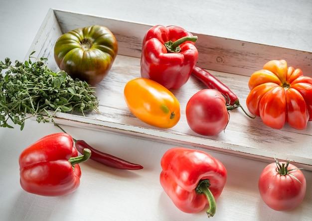 Verse tomaten en paprika's op het houten dienblad