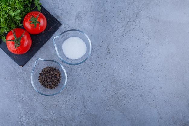 Verse tomaten en peterseliebladeren op zwarte scherpe raad met kruiden.