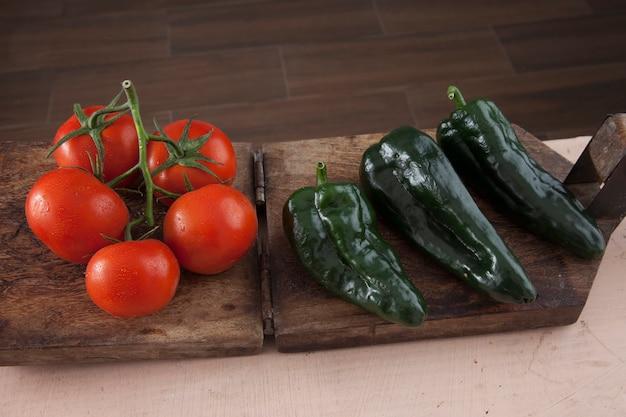 Verse tomaten en poblano pepers op een houten tafel achtergrond a