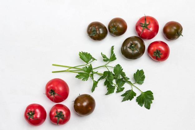 Verse tomaten en takjes peterselie op tafel. witte achtergrond. ruimte kopiëren. plat leggen