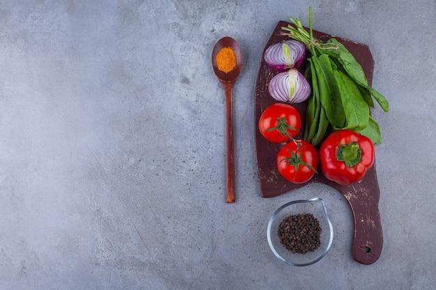 Verse tomaten en ui met verschillende kruiden op een houten bord.