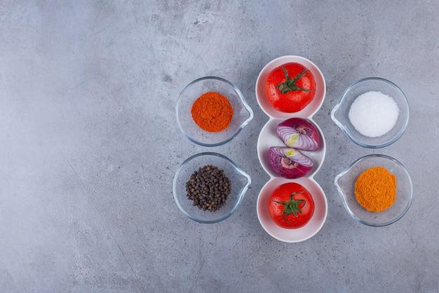 Verse tomaten en ui met verschillende kruiden op stenen oppervlak.