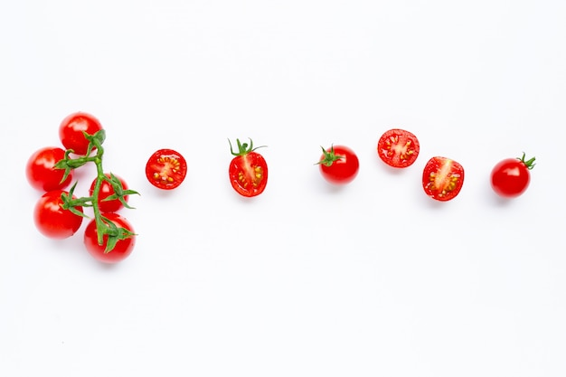 Verse tomaten, gehele en halve die besnoeiing op wit worden geïsoleerd.