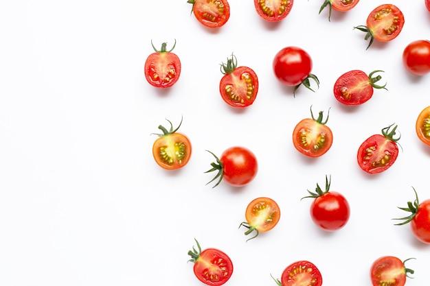 Verse tomaten, gehele en halve die besnoeiing op wit worden geïsoleerd