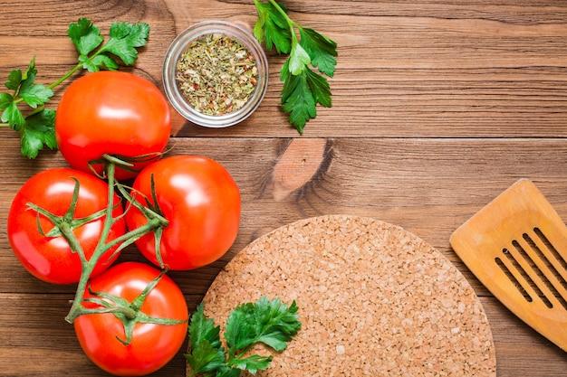Verse tomaten, greens en kruiden op een hout, ruimte voor de inscriptie, top view