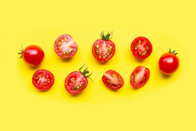 Verse tomaten, hele en halve snee geïsoleerd op geel
