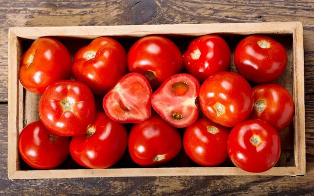 Verse tomaten in een doos op houten tafel