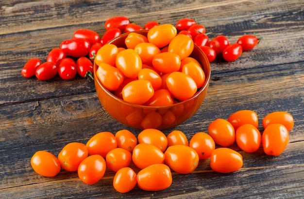 Verse tomaten in een mening van de kom hoge hoek over een houten lijst