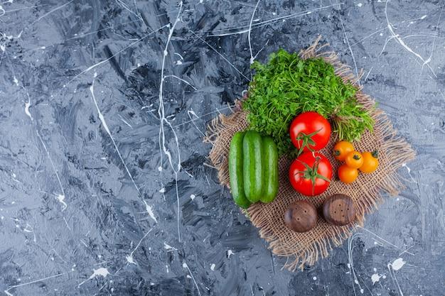 Verse tomaten, komkommers en peterselieblaadjes op marmeren oppervlak.