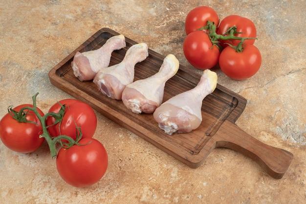 Verse tomaten met houten plank van ongekookte kippenpoten