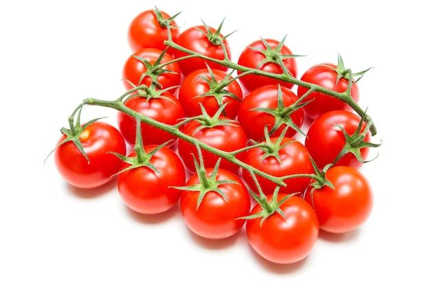 Verse tomaten op de steel op wit wordt geïsoleerd.