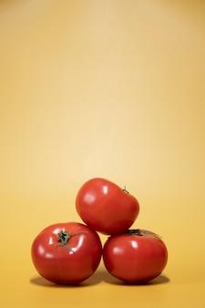 Verse tomaten op een heldere gele achtergrond in een fotostijl van een reclamevoedsel. verticaal frame