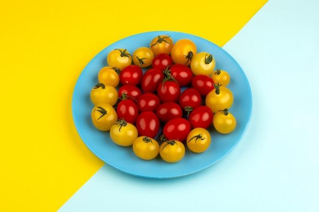 Verse tomaten rijp rood en geel binnen blauwe plaat op het ijsblauwe en gele bureau