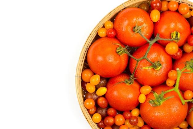 Verse tomaten uit het veld, in een mand op een witte achtergrond.