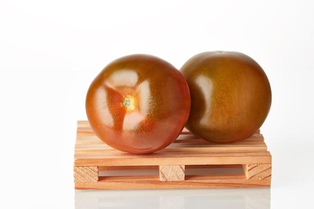 Verse tomatenkumato op logistieke pallet die op vervoer naar bestemmingsplaats wacht die over witte achtergrond wordt geïsoleerd.