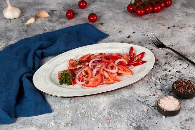 Verse tomatensalade met rode ui, grijze achtergrond