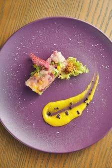 Verse tonijn en zeebaars en coquille tartaar steak met gele saus en mosterd op een paarse plaat op een houten muur. close-up, selectieve aandacht