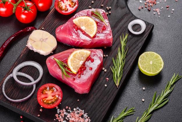 Verse tonijnfilet steaks met specerijen en kruiden op een zwarte ondergrond. tonijn voorbereiden om te bakken