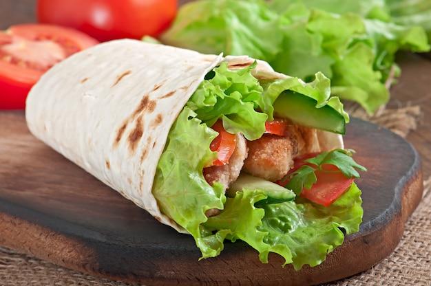 Verse tortillaomslagen met kippengoudklompjes en groenten op plaat