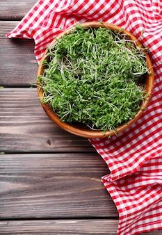 Verse tuinkerssalade in kom op servet en houten planken