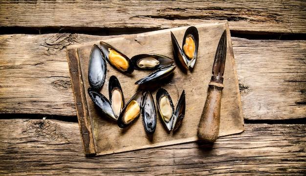 Verse tweekleppige schelpdieren op een houten bord met mes. op houten achtergrond. bovenaanzicht
