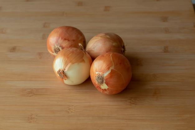 Verse ui. uien, groenten op tafel. food fotografie. gezond eten. vier uien op een tafel op een houten bord.