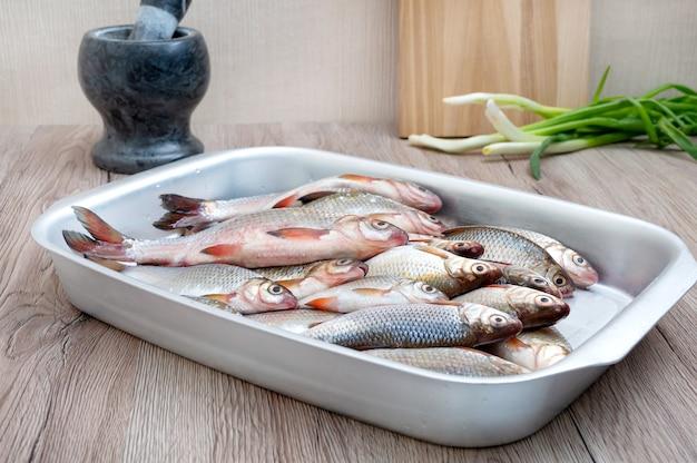 Verse vangst van riviervis in een kom op tafel.