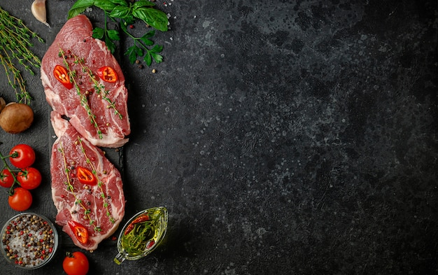 Verse varkenslapjes vlees met hete peper, kruiden en groenten. bovenaanzicht, kopieer ruimte. italiaanse keuken