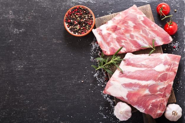 Verse varkensribbetjes met ingrediënten voor het koken op donkere tafel, bovenaanzicht