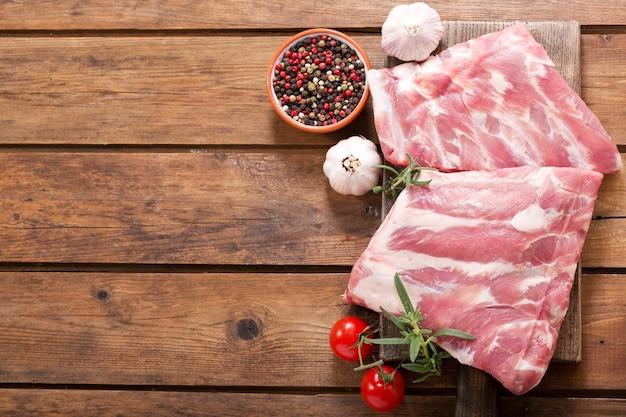Verse varkensribbetjes met ingrediënten voor het koken op houten tafel, bovenaanzicht