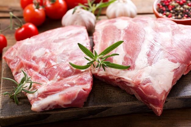 Verse varkensribbetjes met ingrediënten voor het koken op houten tafel