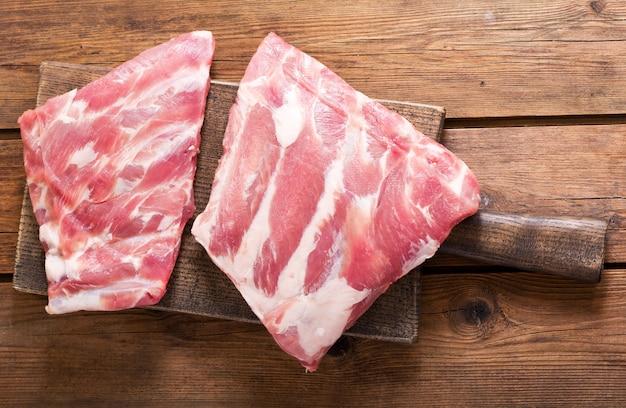 Verse varkensribbetjes op een houten bord, bovenaanzicht