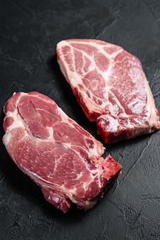 Verse varkenssteak. marmer vlees. zwarte achtergrond. bovenaanzicht