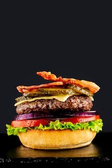 Verse vegetarische smakelijke hamburger op een zwarte achtergrond. een burguer in fasen maken