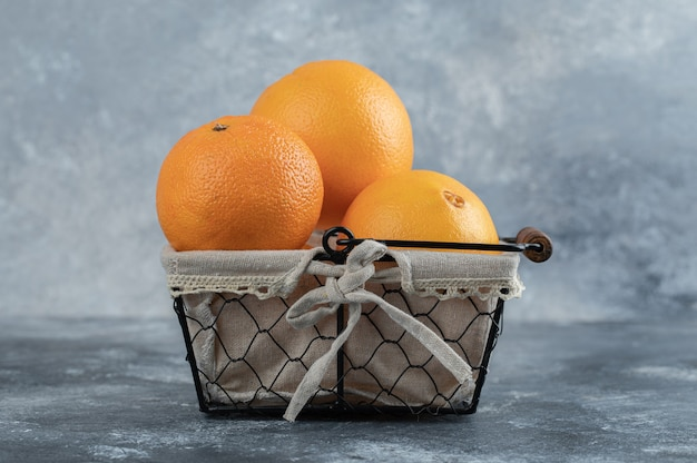 Verse verfrissende sinaasappelen in mand op marmeren tafel.