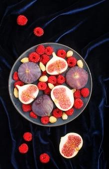 Verse vijgen, aardbeien en frambozen op blauwe plaat en blauw fluweel textiel