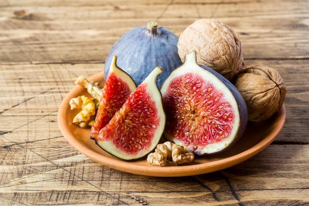 Verse vijgen heel en snijd pitten van walnoten op een bord het oude houten oppervlak.